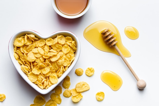 Corn flakes in heart bowl on white