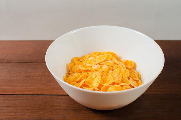 Кукурузные хлопья в белой тарелке. здоровый образ жизни.