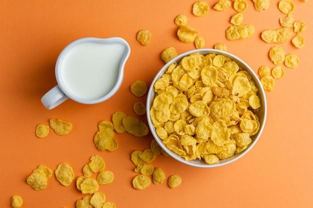 Кукурузные хлопья в шаре и молоке на желтом фоне. вид сверху здорового завтрака.