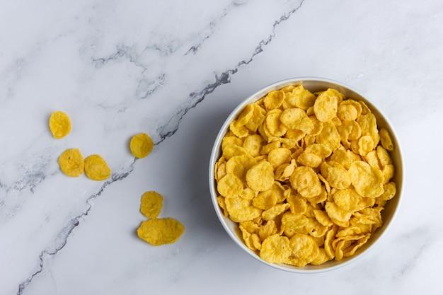 Кукурузные хлопья в миске на мраморной предпосылке. вид сверху здорового завтрака.