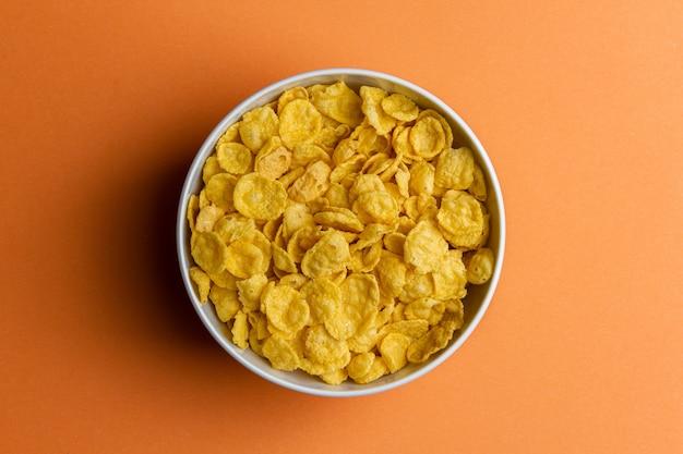 Кукурузные хлопья в шаре на желтом фоне. вид сверху здорового завтрака.