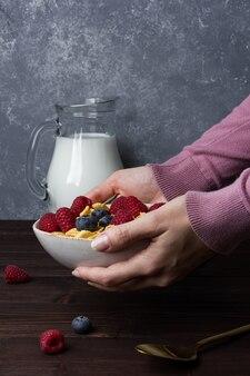 Кукурузные хлопья в миске с ягодами и молоком на деревянном столе. вид сбоку здорового завтрака.