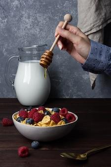 Кукурузные хлопья в миске с ягодами, медом и молоком на деревянном столе. вид сбоку здорового завтрака.