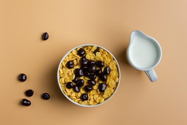 Кукурузные хлопья в миске с шоколадом и молоком на желтом фоне. вид сверху здорового завтрака.