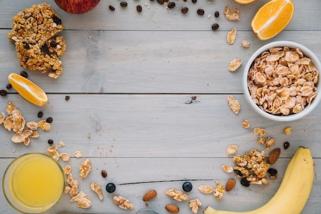 Кукурузные хлопья в миске с фруктами и соком на столе