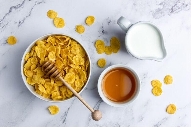 Кукурузные хлопья в миске с молоком и медом на мраморном фоне. вид сверху здорового завтрака.