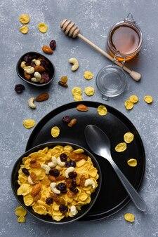 Кукурузные хлопья в шаре с орехами и медом на сером фоне. вид сверху здорового завтрака.
