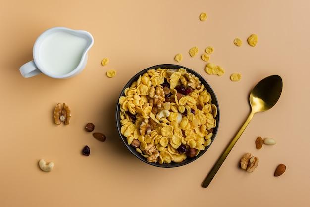 Кукурузные хлопья в миске с орехами и молоком на желтом фоне. вид сверху здорового завтрака.