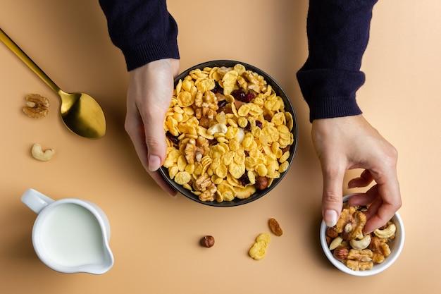 Кукурузные хлопья в миске с орехами, удерживаемые женскими руками на желтом фоне. вид сверху здорового завтрака.