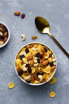 Кукурузные хлопья в шаре с орехами на сером фоне. вид сверху здорового завтрака.