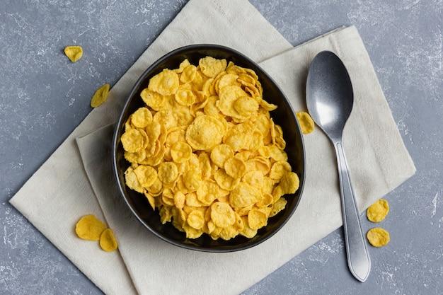 Кукурузные хлопья в миске с ложкой и салфеткой на сером фоне. вид сверху здорового завтрака.