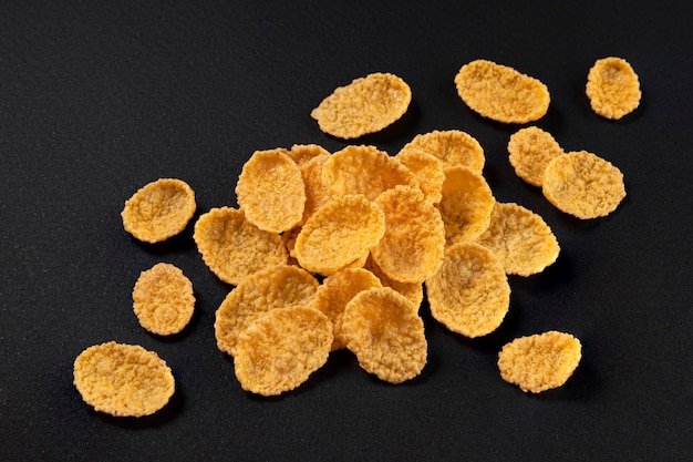 Corn flakes isolated on black background, top view, full depth of field