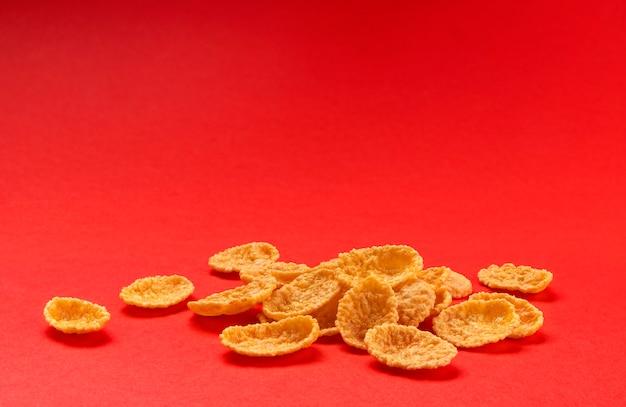 红色背景上孤立的玉米片,一堆传统早餐麦片,一片田野
