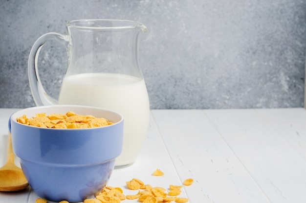 Corn flakes and milk in a glass jug. white wooden table. copy space