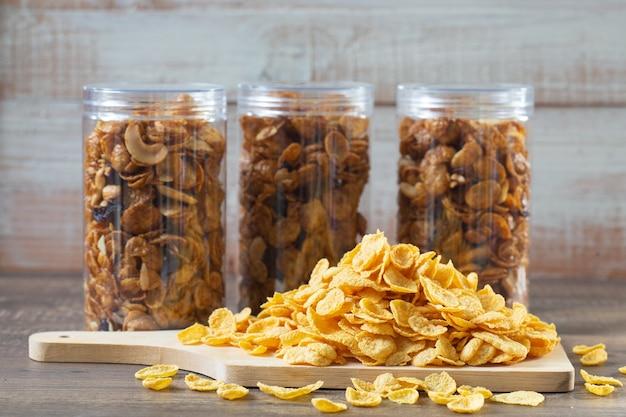テーブルの上の木製まな板上のコーンフレーク(全粒穀物)。