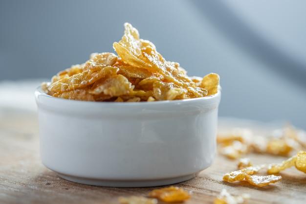 나무 테이블에 흰 그릇에 꿀 콘플레이크. 공간 복사