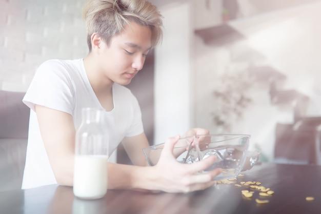 어린 아시아 소년을 위한 아침 식사로 우유를 곁들인 콘플레이크