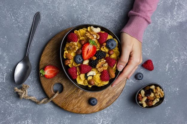 Кукурузные хлопья с орехами и ягодами в миске на сером фоне. женские руки. вид сверху здорового завтрака.