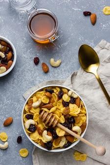 Кукурузные хлопья с орехами и медом в миске на сером фоне. вид сверху здорового завтрака.
