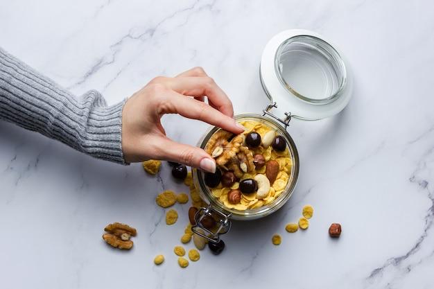 Кукурузные хлопья с орехами в банке, удерживаемые женскими руками на мраморном фоне. вид сверху здорового завтрака.