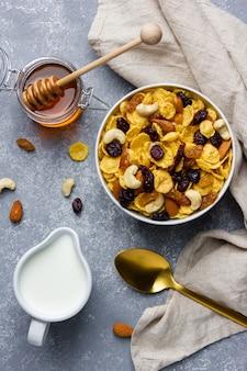 Кукурузные хлопья с орехами, молоком и медом в миске на сером фоне. вид сверху здорового завтрака.