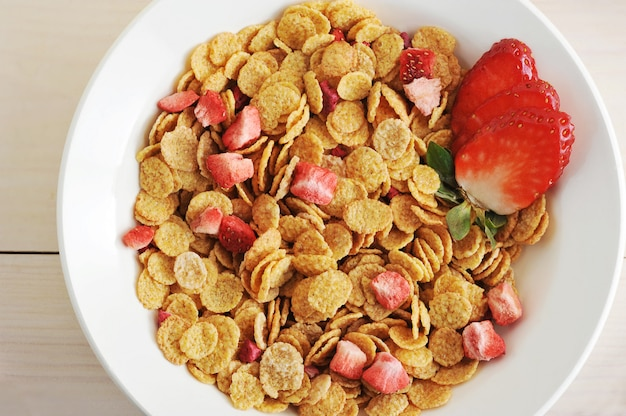 Corn flakes with slices of strawberry in a bowl