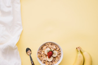 Corn flakes with with fruits in bowl on table