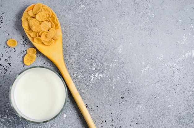 콘 flakesin 콘크리트 배경 및 유리에 우유에 나무로되는 숟가락. 평면 평면도. 공간 복사