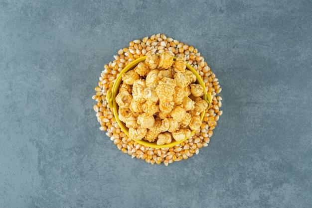 대리석 배경에 카라멜로 코팅된 팝콘 캔디 양동이 주위의 옥수수 알갱이. 고품질 사진