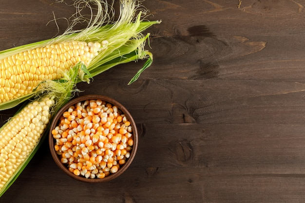 Corn and grains in a clay plate on a dark wooden table. top view.