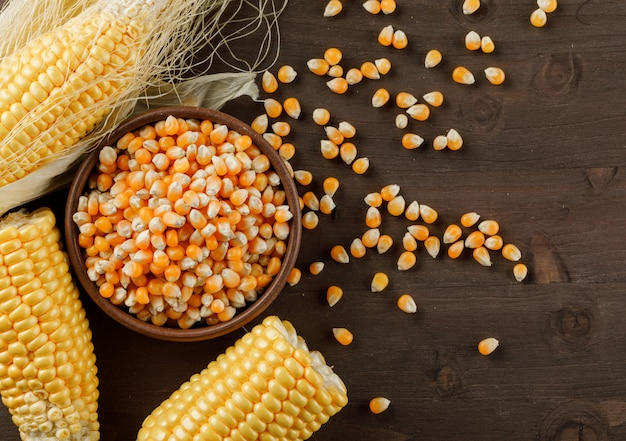 Corn grains in a clay plate with cobs flat lay on a wooden table