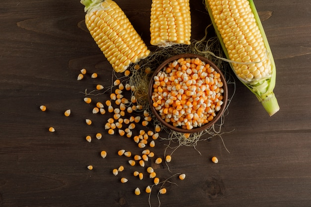 Corn grains in a clay plate with cobs top view on a wooden table