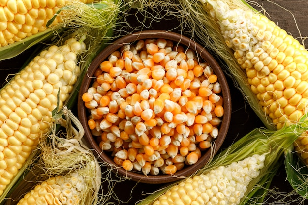 Corn and grains in a clay plate on wooden table, flat lay.