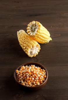 Corn grains with slices in a clay plate on wooden table, high angle view.