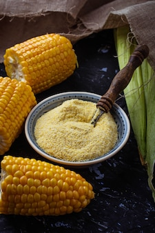 Corn grits and corncob on concrete background. selective focus