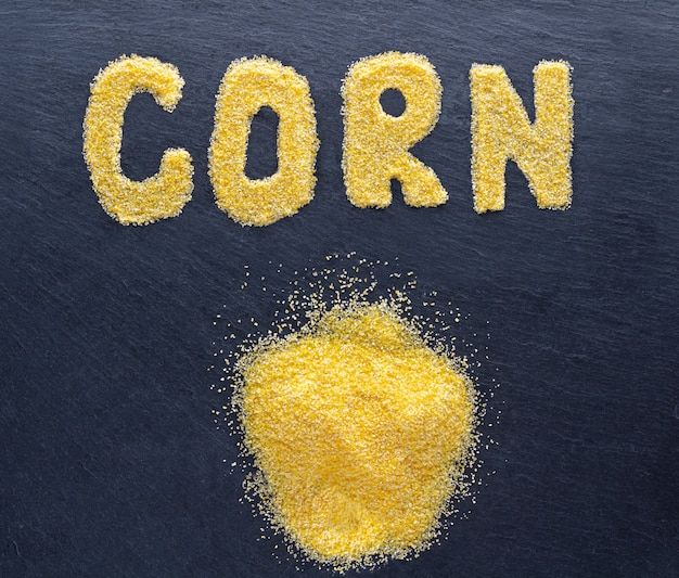 Corn grits on dark stone background. top view.