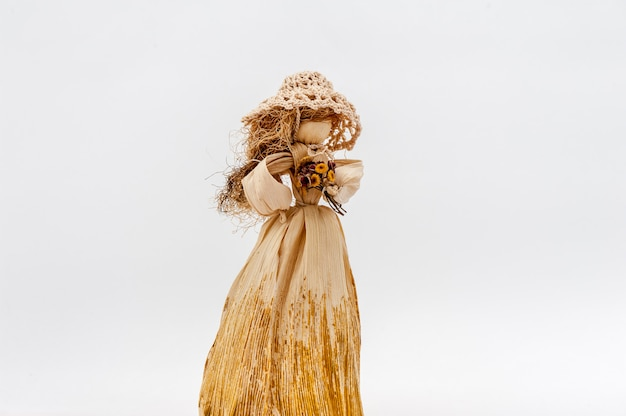 Corn husk doll hands with flowers on white