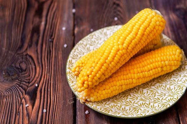 Кукуруза в тарелку на темный деревянный стол. высокий угол обзора.
