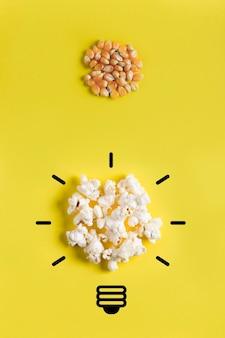 トウモロコシの実と電球を描いたポップコーン。進化の概念、アイデア、ブレーンストーミング、創造的なプロセス。