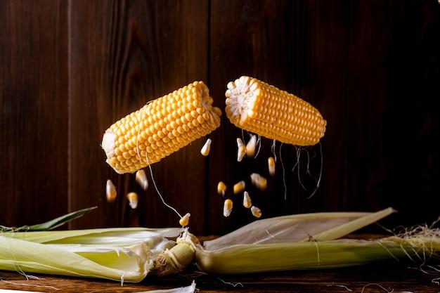 옥수수 부상. 신선한 옥수수 머리가 반으로 갈라지고 개별 곡물이 어두운 나무 배경에 날아갑니다.