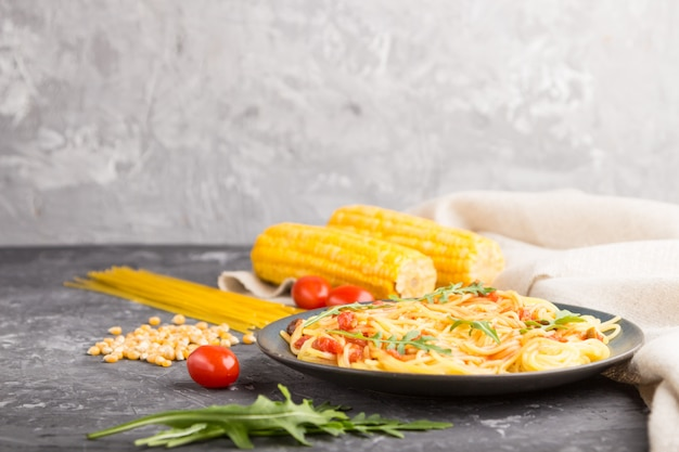 Лапша кукурузная с томатным соусом и рукколой на черном фоне бетона. вид сбоку, копия пространства.