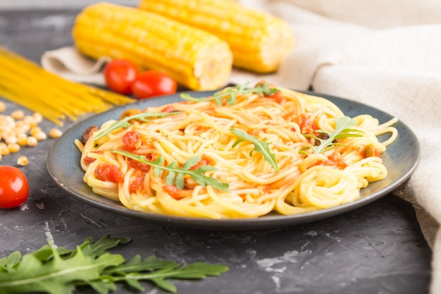 Corn noodles with tomato sauce and arugula on a black concrete surface and linen textile