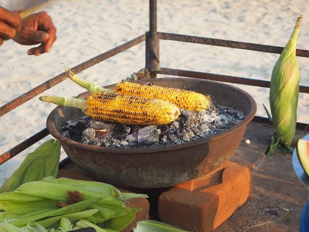 개 암 나무 열매에 옥수수는 향기로운 향신료와 함께 석탄에 튀겨집니다. 인도의 맛있고 건강한 간식