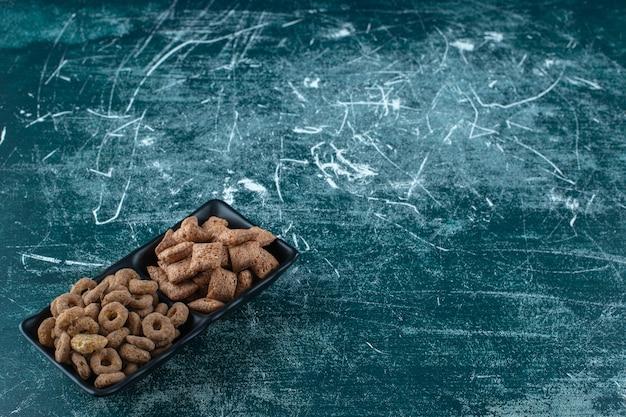 파란색 배경에 그릇에 옥수수 패드와 옥수수 반지. 고품질 사진