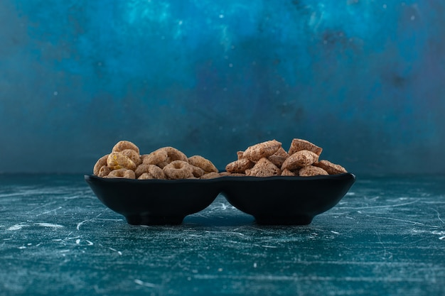 Cuscinetti di mais e anelli di mais in una ciotola, sullo sfondo blu. foto di alta qualità