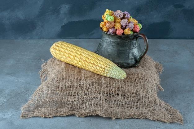 Кукуруза и разноцветный ароматный попкорн в металлическом горшке. фото высокого качества
