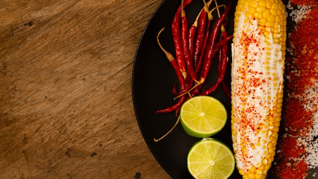 Corn on plate with limes and peppers
