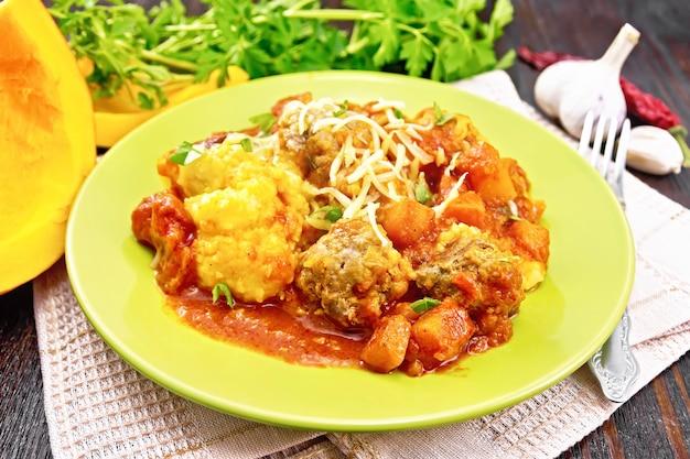 ミートボール、トマト、ニンニク、カボチャのソース、木の板の背景のキッチンタオルのプレートにチーズとパセリを振りかけたトウモロコシのお粥