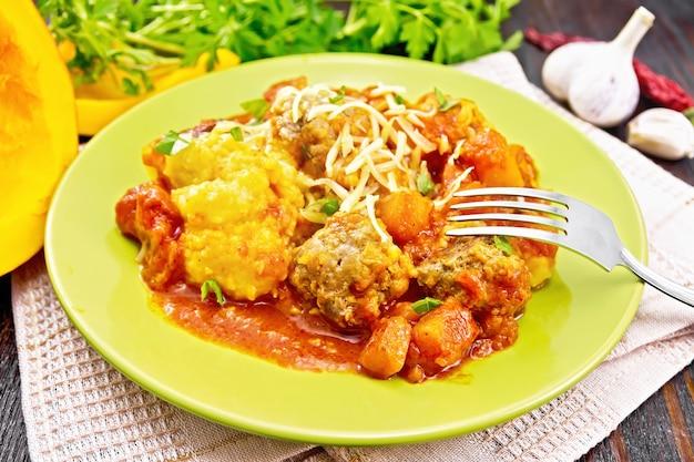 木の板の背景にナプキンのプレートにチーズとパセリをまぶしたミートボール、トマト、ニンニク、カボチャのソースとトウモロコシのお粥