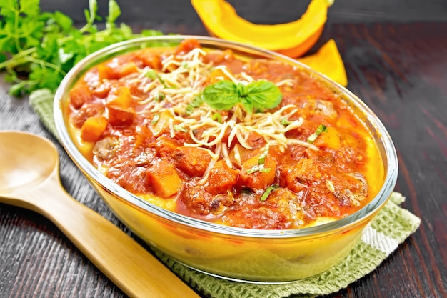 ミートボール、トマト、ニンニク、カボチャのソース、チーズを振りかけたトウモロコシのお粥、木の板の背景にタオルの上の鍋にバジル